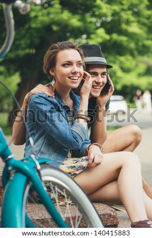 Happy girl and boy sitting on the stairs. Outdoors - stock photo