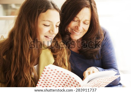 Happy girl and grandmother studying - stock photo