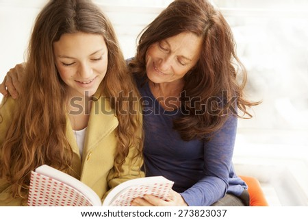 Happy girl and grandmother studying, reading a book - stock photo