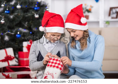 Happy girl and her brother  in Santa hat with Christmas sock. - stock photo