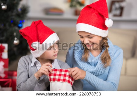 Happy girl and her brother  in Santa hats with Christmas sock. - stock photo
