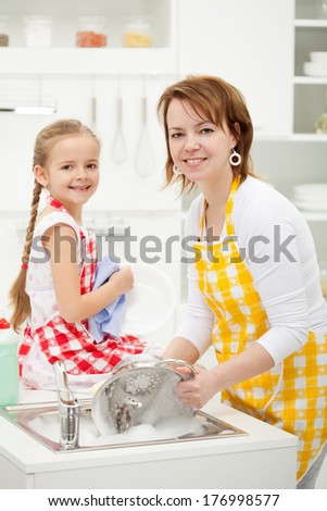 Happy girl and mother washing dishes together wearing aprons - stock photo