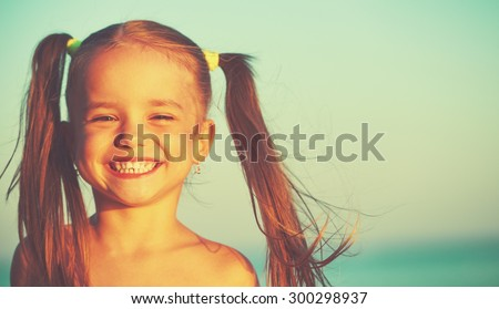 happy girl child on the beach by the sea - stock photo
