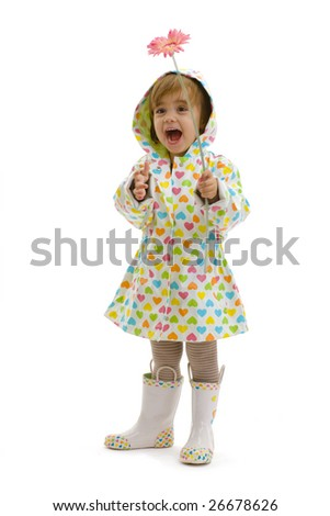 Happy girl child wearing raincoat and boots, holding pink flower, laughing. Isolated on white background. - stock photo