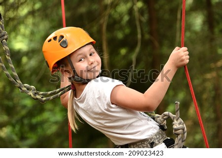 Happy girl climbing in the trees  - stock photo
