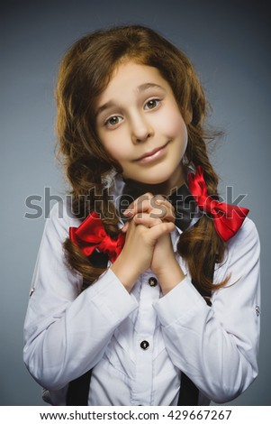 Happy girl. Closeup Portrait of handsome teen pleading or beging on grey background - stock photo