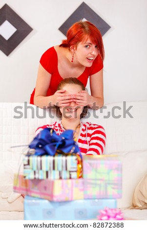 Happy girl covering girlfriends eyes for a surprise at living room - stock photo