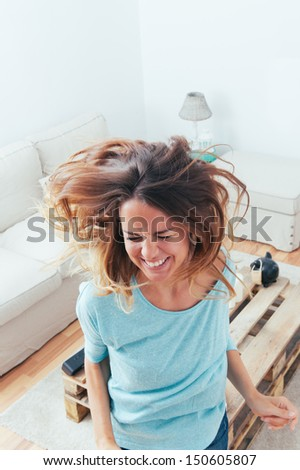 Happy girl dancing at home while listen music with headphones. She is in her home - stock photo