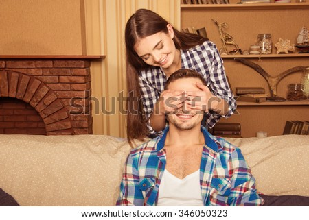 happy girl did surprise her boyfriend, covering his eyes with her hands - stock photo