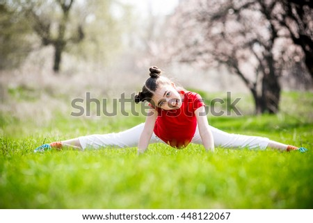 happy girl doing stretching exercises in park in spring. cheerful girl does the splits on the grass - stock photo