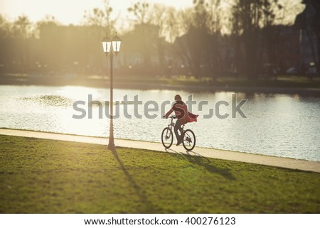 happy girl drives on bike near pond. image with tilt-shift effect - stock photo
