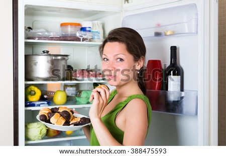 Happy girl eating cake from fridge  at home - stock photo