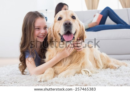 Happy girl embracing Golden Retriever while lying on rug at home - stock photo