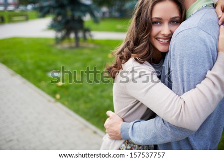 Happy girl embracing her boyfriend and looking at camera in park - stock photo