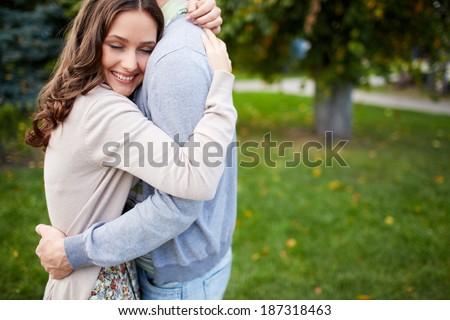 Happy girl embracing her boyfriend in park - stock photo