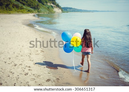 Happy girl enjoying sunny day at the beach. Running with balloons - stock photo