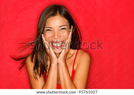 Happy girl excited. Young woman smiling very happy surprised holding head being amazed on red background. Funky young multicultural Caucasian / Chinese Asian female model joyful on red background. - stock photo