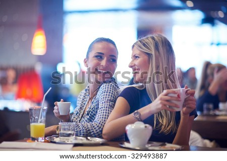 happy girl friends have cup of coffee in modern city restaurant - stock photo