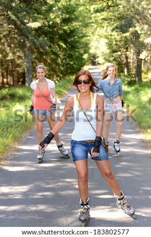 Happy girl friends skating outdoors on countryside road summer sport - stock photo