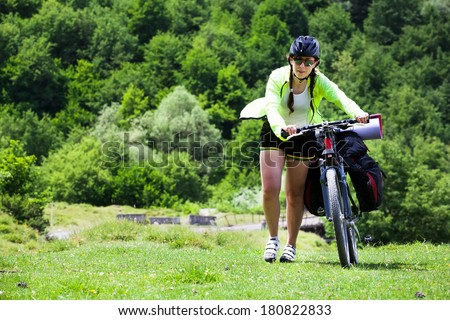 happy girl goes with the bike on the grass to rest in a park.  - stock photo