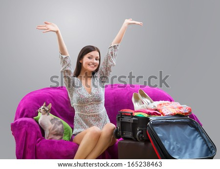 Happy girl going on vacation, studio shot on gray background - stock photo