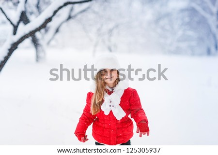 Happy girl having fun outdoors on snowing winter day and looking at the camera - stock photo