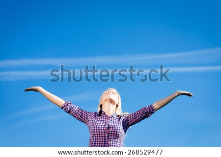 Happy girl having fun standing in the field hands up on blue sky copy space background - stock photo