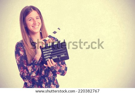 Happy girl holding a clapperboard - stock photo