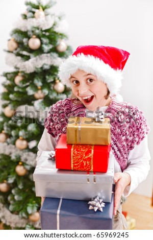 Happy girl holding a lot of presents in front of Christmas tree - stock photo
