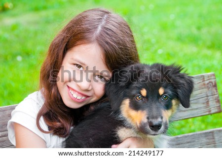 Happy girl holding a puppy of Australian shepherd - stock photo