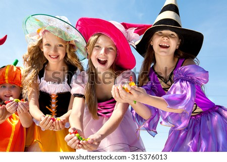 Happy Girl Holding Candies in Halloween Costumes of Witches and Pumpkin at the Blue Sky. - stock photo