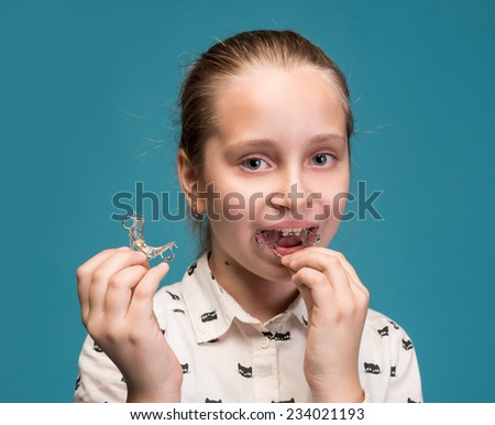 Happy girl holding dental braces on a blue background - stock photo