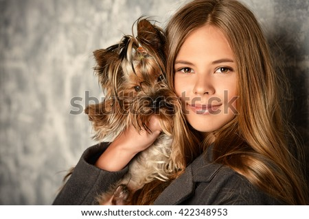Happy girl holding her lovely yorkshire terrier dog.  - stock photo