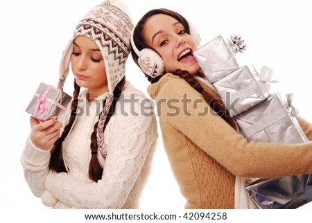 Happy girl holding large stack of gifts and sad girl with tiny gift - stock photo