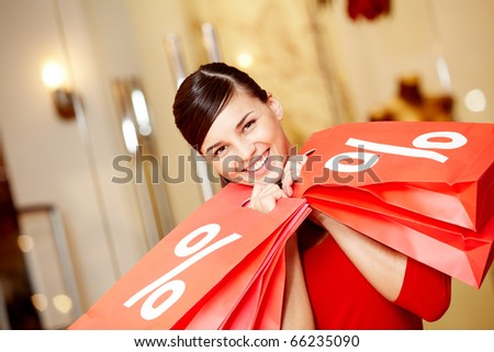 Happy girl holds red paperbags with symbol of sale and looking at camera - stock photo