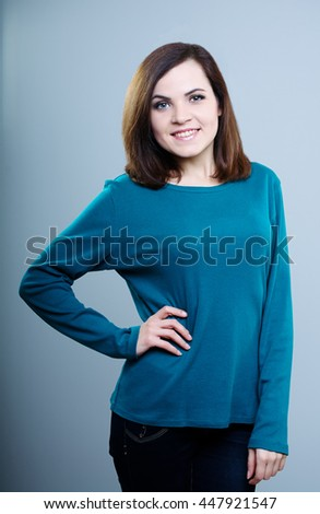 happy girl in a blue shirt holds hand on your belt and smiling on a gray background - stock photo