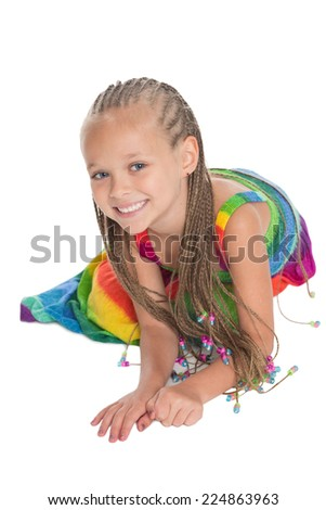 Happy girl in a colorful dress sitting on the floor. Girl six years. - stock photo