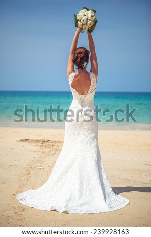 happy girl in a wedding dress with a bouquet by the sea - stock photo