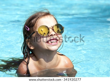Happy girl in mirrored sunglasses in the pool looking at the sky in the sun - stock photo