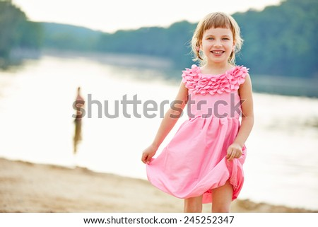 Happy girl in pink dress in summer on a beach - stock photo