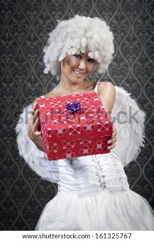 Happy girl in white angel costume with colorful gift box. - stock photo