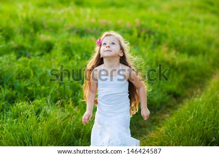 Happy girl in white dress running on the meadow - stock photo
