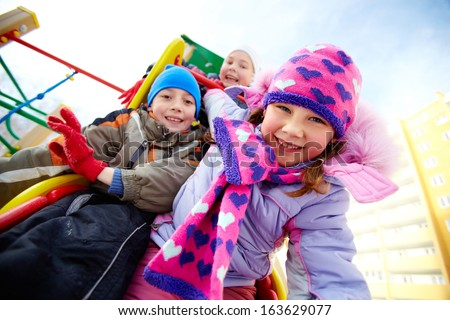 Happy girl in winterwear playing outside with her friends on background - stock photo