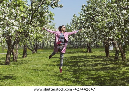 Happy girl jumping in the garden - stock photo