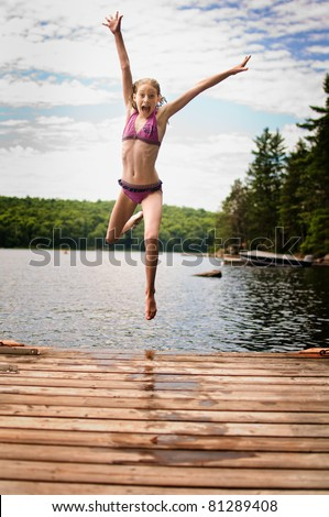 happy girl jumping off a dock into a lake - stock photo