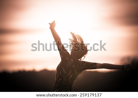 Happy girl jumping on the dawn time.Happy woman jumps to the sky in the yellow meadow at the sunset.Happy woman jumping against sunset. Freedom concept. Enjoyment. - stock photo