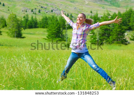 Happy girl jumping on the field, enjoying fresh air and spring green grass, freedom and happiness concept - stock photo
