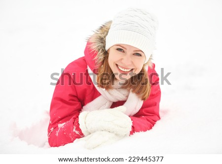 happy girl laughs while lying on the snow in the winter outdoors - stock photo