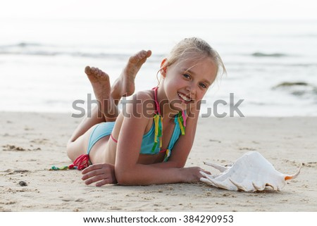 Happy girl listening to the seashell. - stock photo