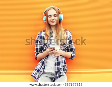 Happy girl listens and enjoys good music in headphones over colorful orange background - stock photo